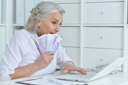Senior doctor sitting at table with laptop and holding money
