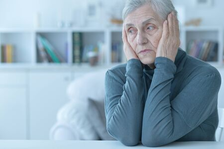 Portrait of tired senior woman at home Фото со стока