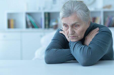 Portrait of sad senior woman sitting at table