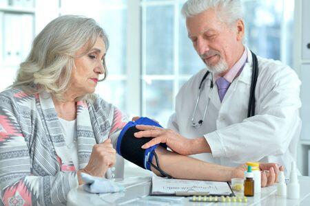Portrait of elderly doctor measuring blood pressure
