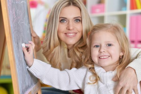 Portrait of mother with little daughter writing on blackboard Banque d'images