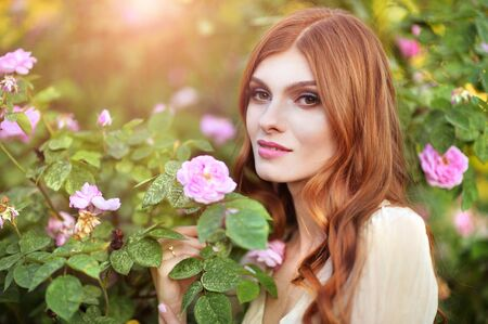 Portrait of beautiful young woman posing by rose bush in summer park