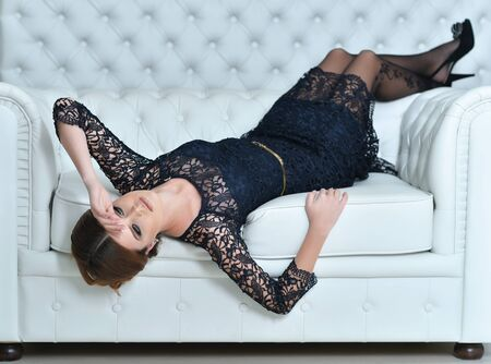 Beautiful young woman in black dress on sofa Banque d'images