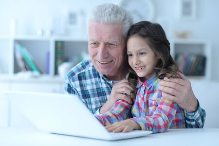 Emotional senior man with granddaughter using laptop at home