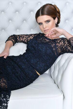 Beautiful young woman in black dress sitting on sofa