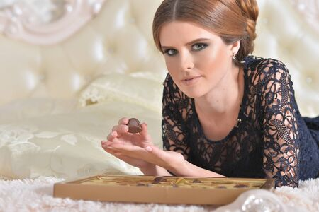 Beautiful young woman on bed with chocolates