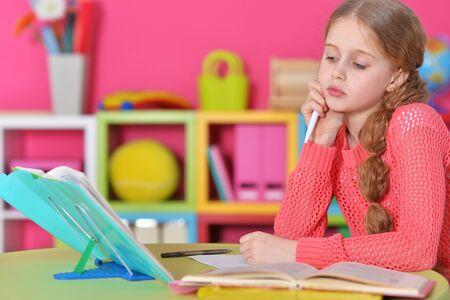 Cute schoolgirl doing homework at her room