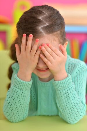 Portrait of cute little girl covering face with hands