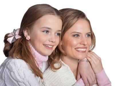Schöne Mutter umarmt ihre Tochter auf weißem Hintergrund
