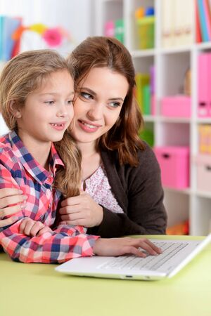 Portrait of mother and daughter using laptop together