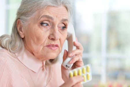 Sick senior woman with medicine calling to hospital Standard-Bild