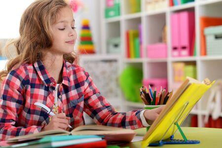 Cute teen girl doing homework in her room