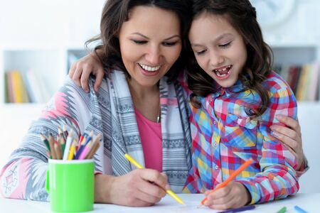 Little cute girl with mother drawing at the table at home