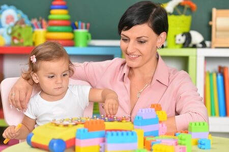 Young mother and little daughter playing lego game Foto de archivo