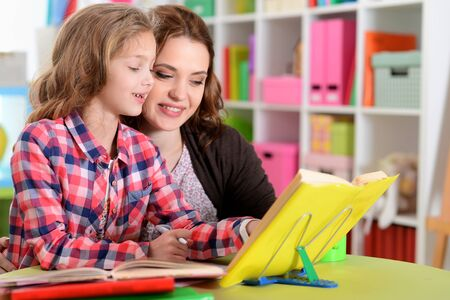 Beautiful little cute girl with mother doing homework