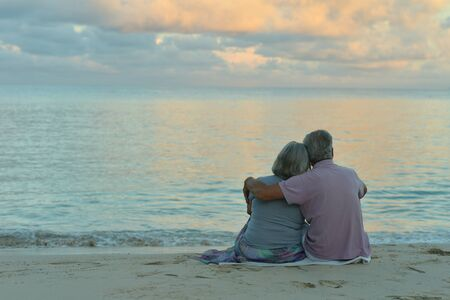Back view. Happy elderly couple resting on tropical beach