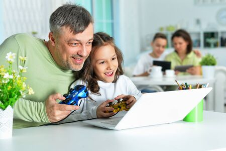 Father with little daughter using laptop playing game