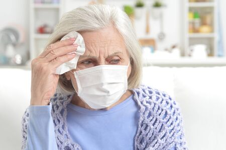 Ill beautiful senior woman with facial mask