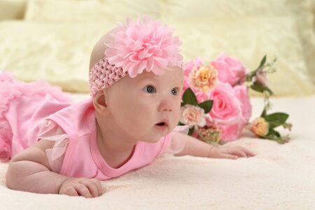 Cute little baby girl on bed with flowers Foto de archivo