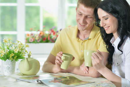 Portrait of happy young couple reading interesting book