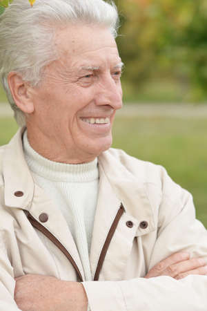 Portrait of happy smiling senior man in park