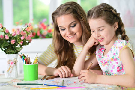 Portrait of girl with mother drawing at home Banque d'images