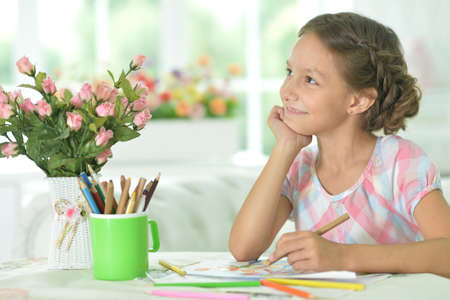 Portrait of cute girl drawing picture at home
