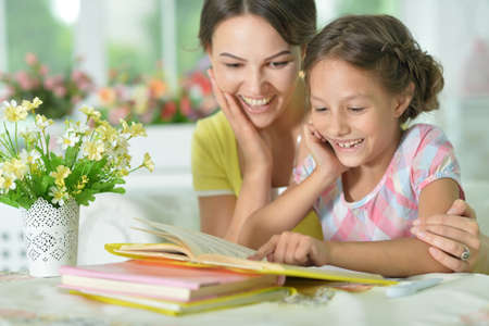 Little cute girl reading book with mother at the table at home Standard-Bild