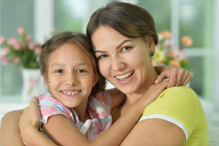 Portrait of a charming little girl hugging with mom at home