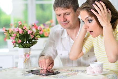 Surprised young couple sitting at table and looking at digital tablet