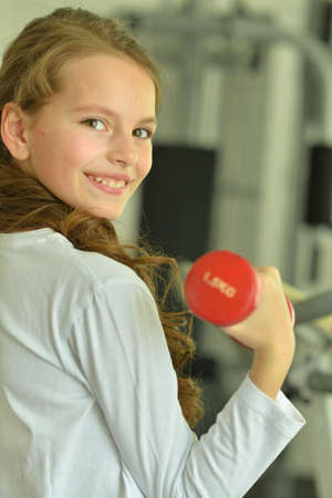 Little girl doing exercises with dumbbell in gym