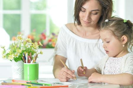 Cute girl with mother drawing at the table