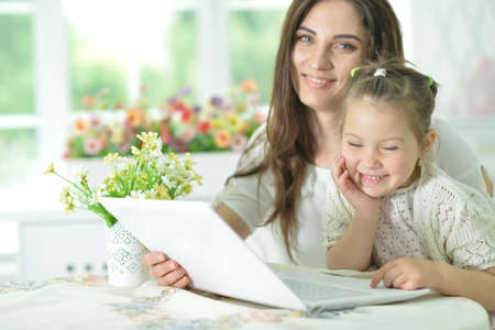 Happy mother and daughter using laptop together