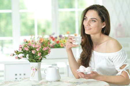 Young beautiful woman holding white cup at home 版權商用圖片