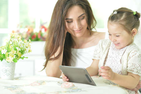 Happy mother and daughter using tablet together at home