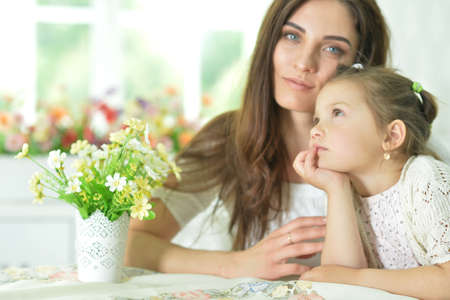 Portrait of a charming little girl with mom at home