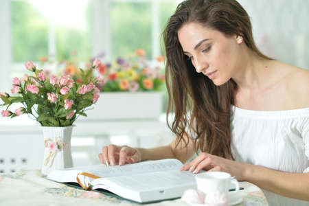 Young attractive woman with book and cup of coffee