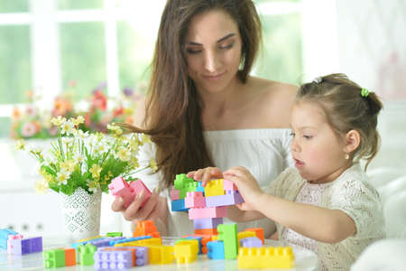 Little daughter and happy mother playing with colorful plastic blocks