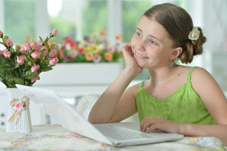Happy cute girl using laptop at home 免版税图像