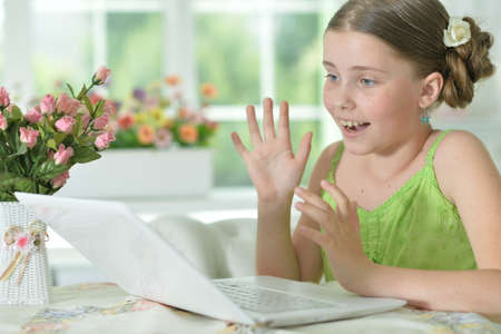 Surprised cute girl using laptop at home