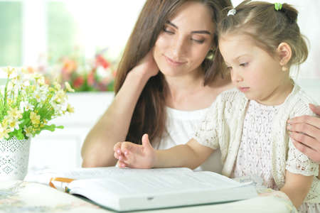 Portrait of little cute girl with mother reading book at home
