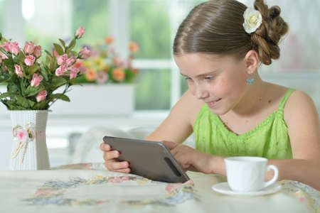 Portrait of beautiful little girl with tablet pc