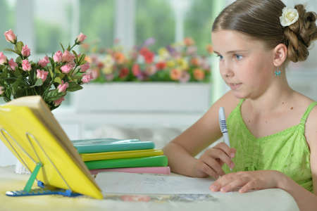 Portrait of little cute girl doing homework at home