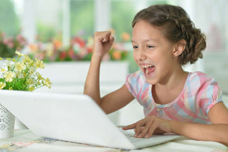Emotional happy cute girl using laptop at home