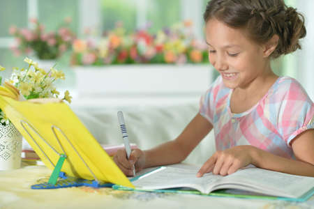 Little cute girl doing homework at home