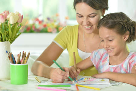 Cute girl with mother drawing at the table at home