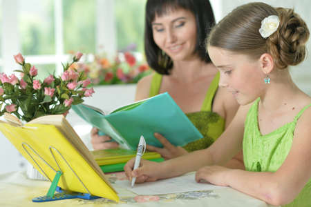 Cute girl and mother doing homework at home