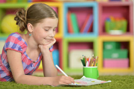 Portrait of beautiful girl drawing picture at home