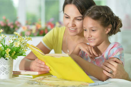 Cute girl reading book with mother at the table at home