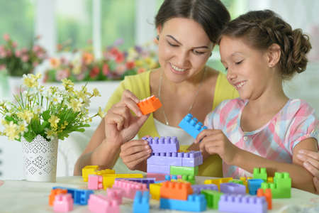 Daughter and mother playing with colorful plastic blocks at home Stock fotó